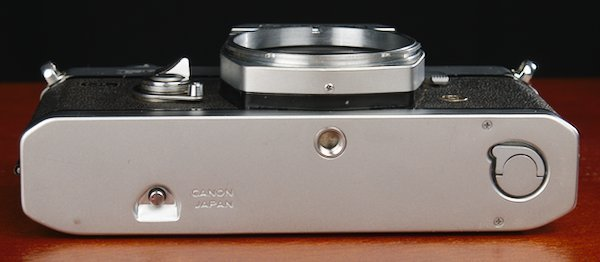 Bottom plate of the Canon 35mm camera with the film rewind lock and film door switch.